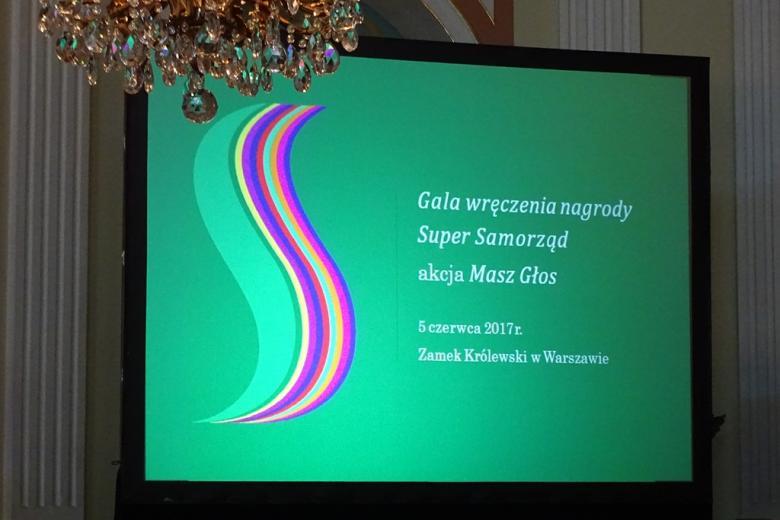 zdjęcie: telebim, na którym na zielonym tle widnieje biały napis: Gala wręczenia Nagrody Super Samorząd akacja Masz Głos