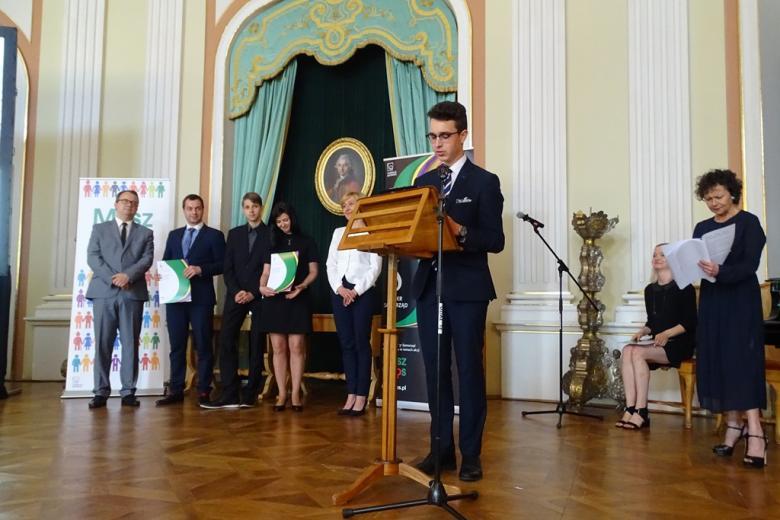 zdjęcie: przy mównicy stoi młody mężczyzna w garniturze, za nim kilka osób