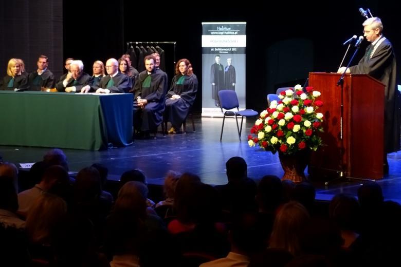 zdjęcie: na scenie przy mównicy stoi mężczyzna w todze, po lewej stronie widać osoby w togach siedzące za stołem