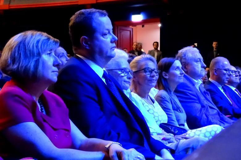 zdjęcie: kilka osób siedzi na widowni w pierwszym rzędzie pod sceną