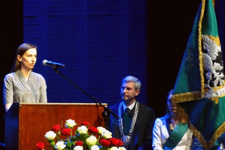 zdjęcie: po lewej stronie, za mownicą stoi kobieta, po prawej widać fragment sztandaru adwokatury