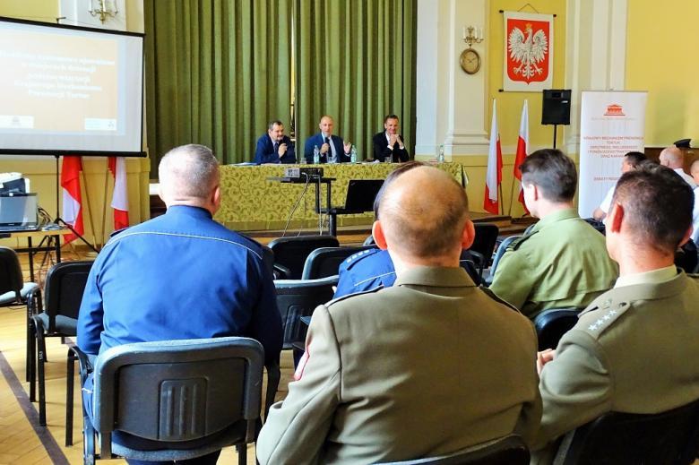 zdjęcie: na pierwszym planie mężczyźni w zielonych mundurach, przed nimi za stołem siedzi trzech mężczyzn