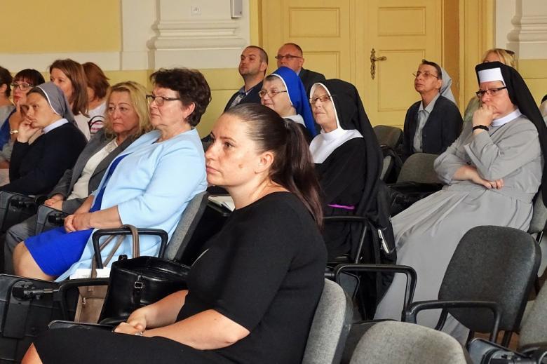 zdjęcie: kilka osób siedzi na sali, w tym siostry zakonne
