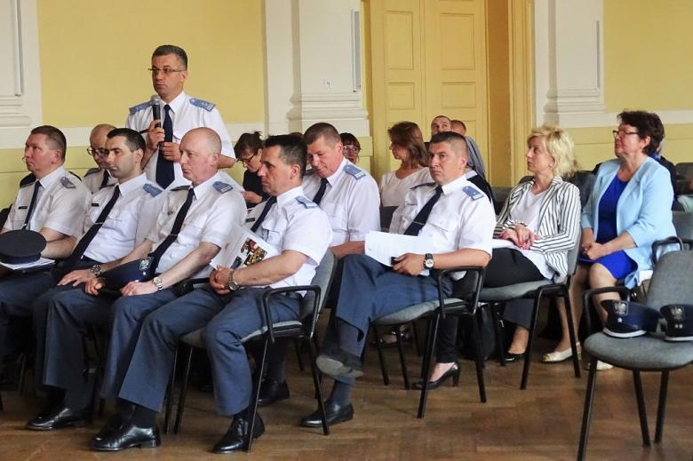 zdjęcie: kika osób w białych koszulach siedzi, jeden z mężczyzn stoi pośrodnicg i mowi do mikrofonu