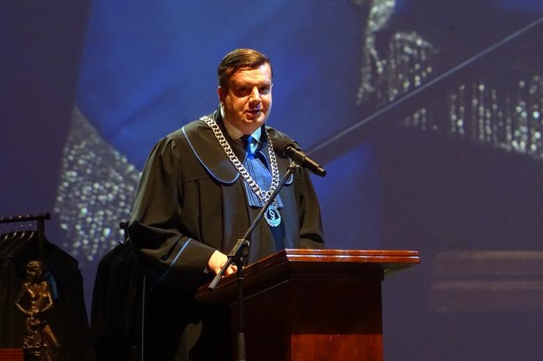 zdjęcie: mężczyzna w todze z niebiekiem żabotem stoi za mównicą