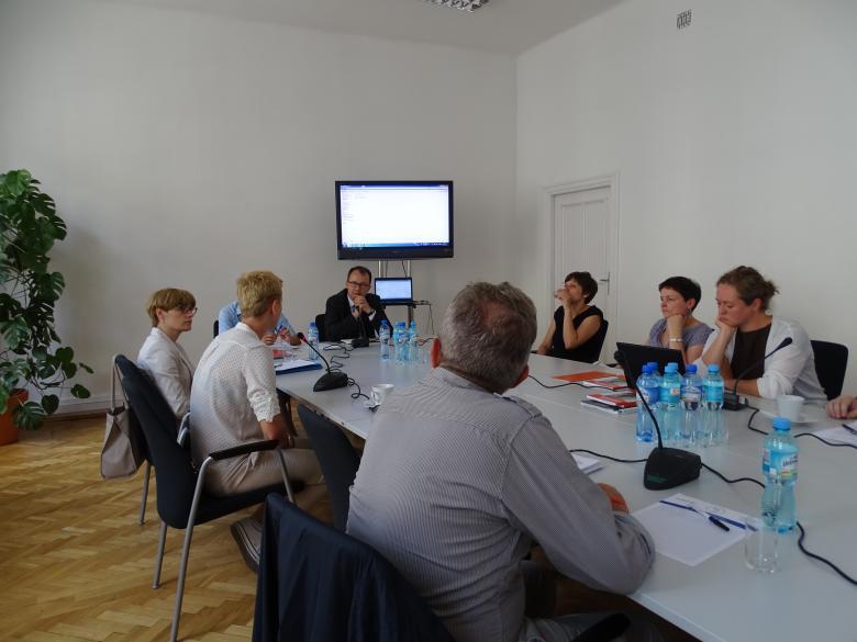 Zdjęcie: ludzie siedzą przy stole, w głębi - ekran