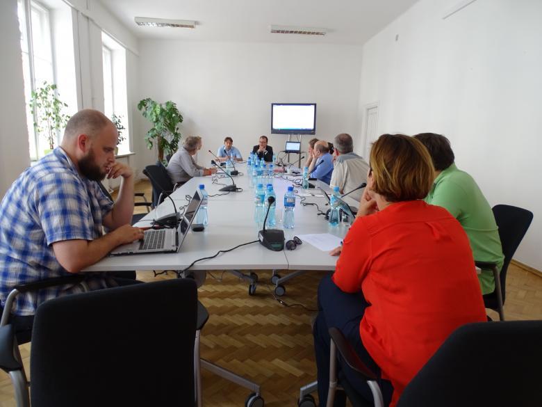 Zdjęcie: ludzie siedzą przy stole, w głębi - ekran, na pierwszym planie - kobieta w czerwieni