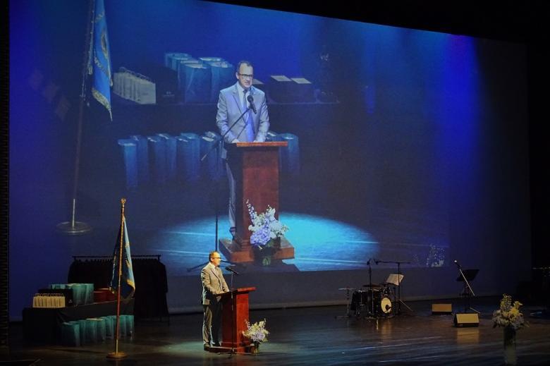 zdjęcie: na scenie za mównicą stoi mężczyzna w garniturze za nim ogromny ekran