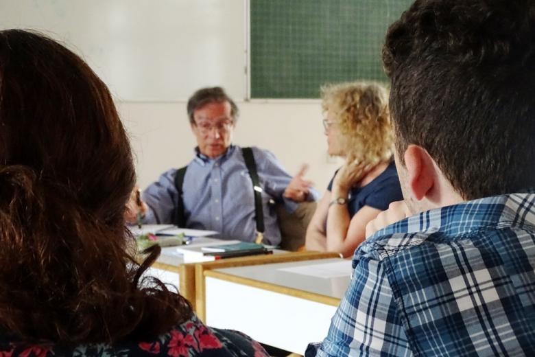 zdjęcie: na pierwszym planie widać od tyłu dwie osoby, pomiędzy nimi w tle widać gentykulującego mężczyznę i siedzącą obok kobietę