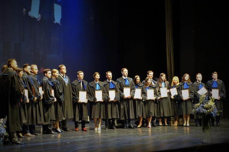 zdjęcie: na scenie stoi kilkanaście osób w togach