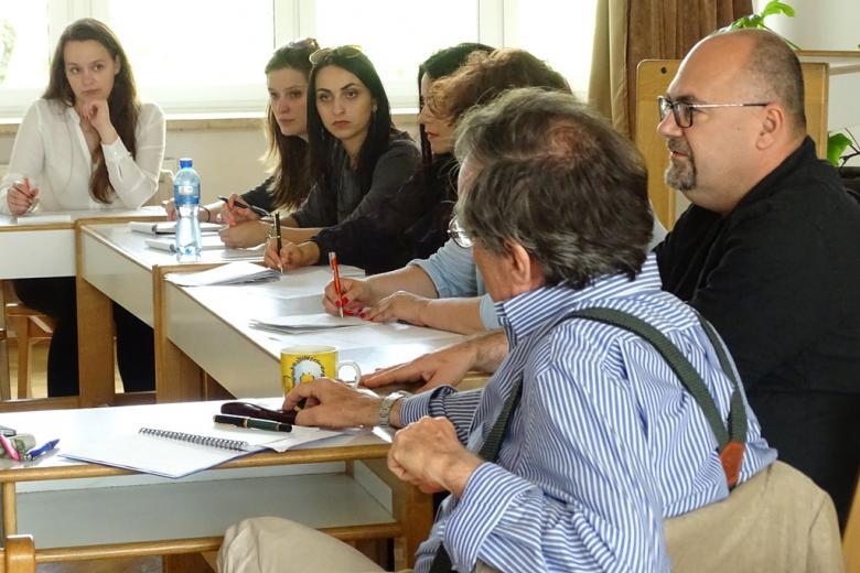 zdjęcie: kilka osób siedzi przy stołach ustawionych w kwadrat, dwaj mężczyźni siedzą tyłem, po prawej stronie widać osoby siedzące bokiem