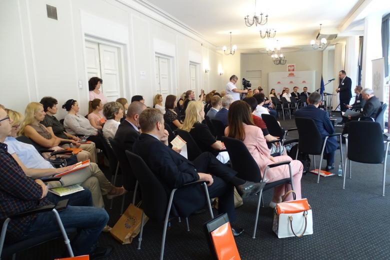 zdjęcie: kilkadzisieąt osób siedzi na sali, przy mównicy stoi mężczyzna w garniturze
