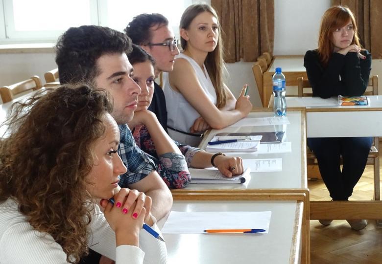 zdjęcie: kilka osób siedzi po lewej stronie stołu, na pierwszym planie kobieta z kręconymi włosami