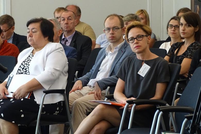 zdjęcie: kilka osób siedzi na sali konferencyjnej