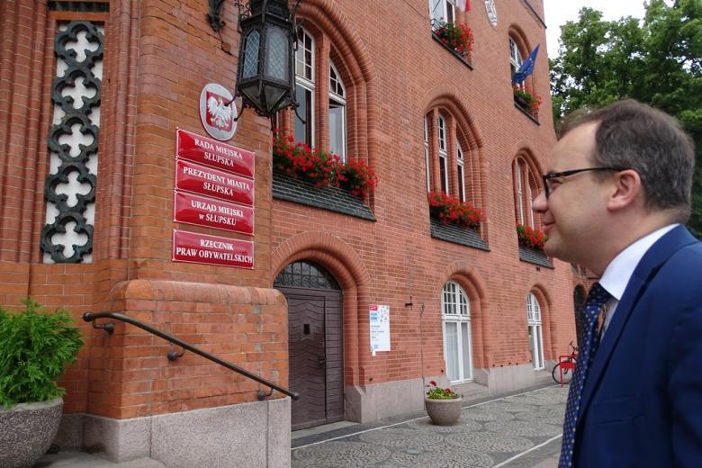 Zdjęcie: mężczyzna przed budynkiem z cegły z tablicami instytucji, które się tu mieszczą