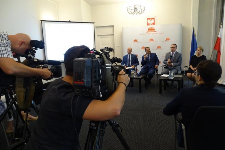 zdjęcie: kobieta i trzech mężczyzn siedzą na przesłach przed nimi dwie kamery i operatorzy