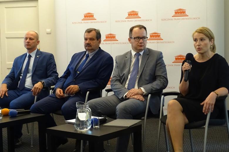 zdjęcie: trzech mężczyzn i kobieta siedzą na krzesłach, kobieta mówi do mikrofonu, za nimi pomarańczowo-biały baner