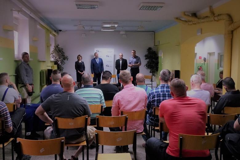 zdjęcie: kilkunastu mężczyzn siedzi tyłem, przed nimi stoją trzej mężczyźni i kobieta