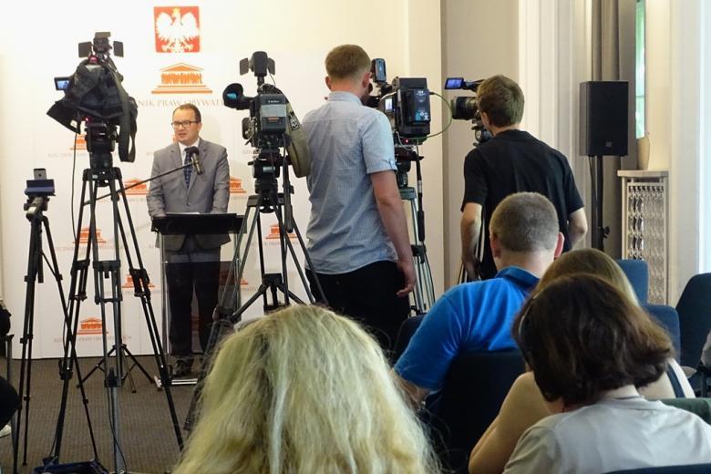 zdjęcie: na pierwszym planie siedzi kilka osób, w tle widać kamery i stojącego przed nimi mężczyznę