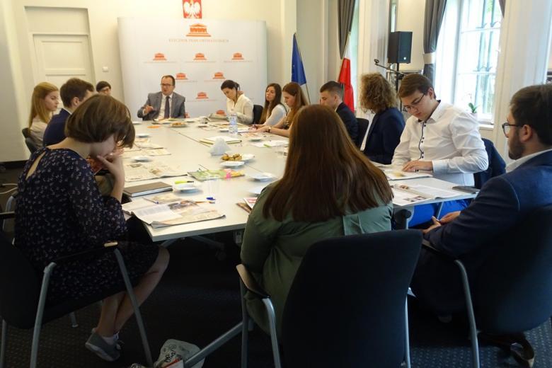 zdjęcie: kilkanaście osób siedzi przy stole i przegląda gazety