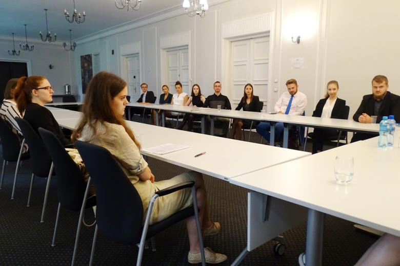 zdjęcie: przy stołach siedzi kilkanaście osób
