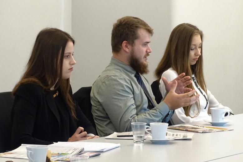 zdjęcie: przy stole siedzą dwie kobiety i mężczyzna, który gestykuluje