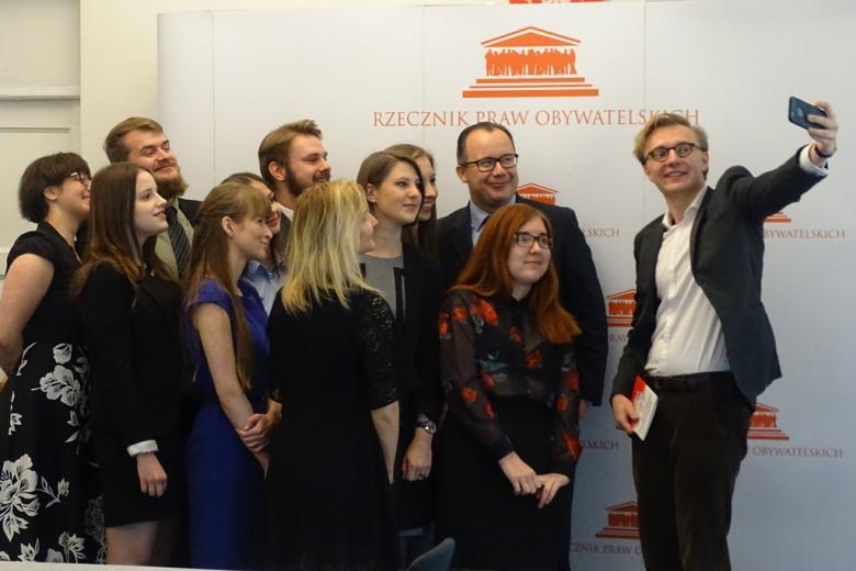 zdjęcie: kilka osób stoi na tle ścianki i pozuje do zdjęcia robionego telefonem komórkowym