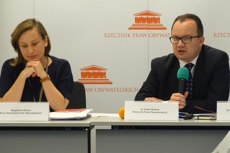 zdjęcie: przy stole siedzi kobieta i mężczyzna, który mówi do mikrofonu