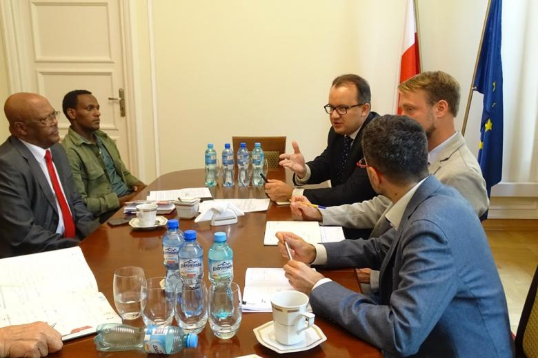 zdjęcie: kilka osób siedzi przy stole, jeden z mężczyzn wskazuje na jedną z osób