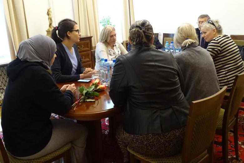 zdjęcie: przy stole siedzi kilka osób, przed jedną z kobiet leżą róże