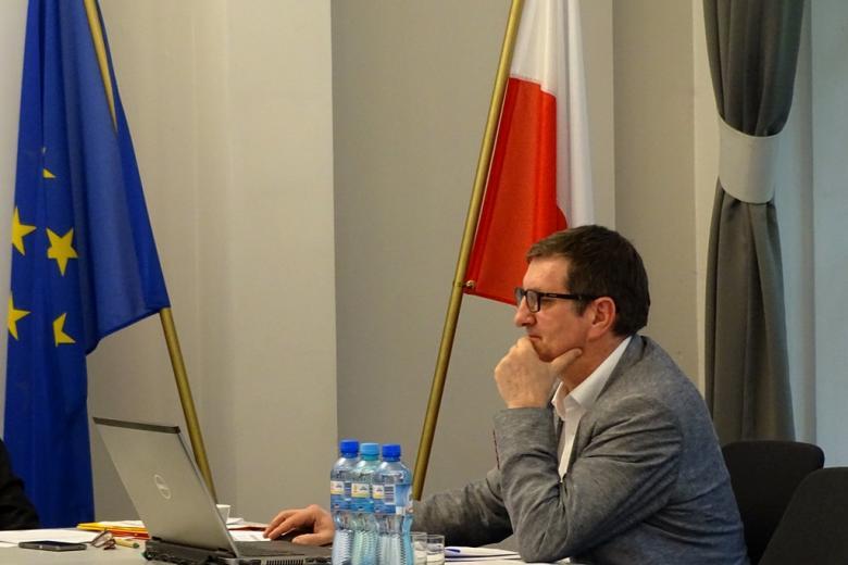 zdjęcie: mężczyzna siedzi prz białych stołach, za nim flagi Polski i UE