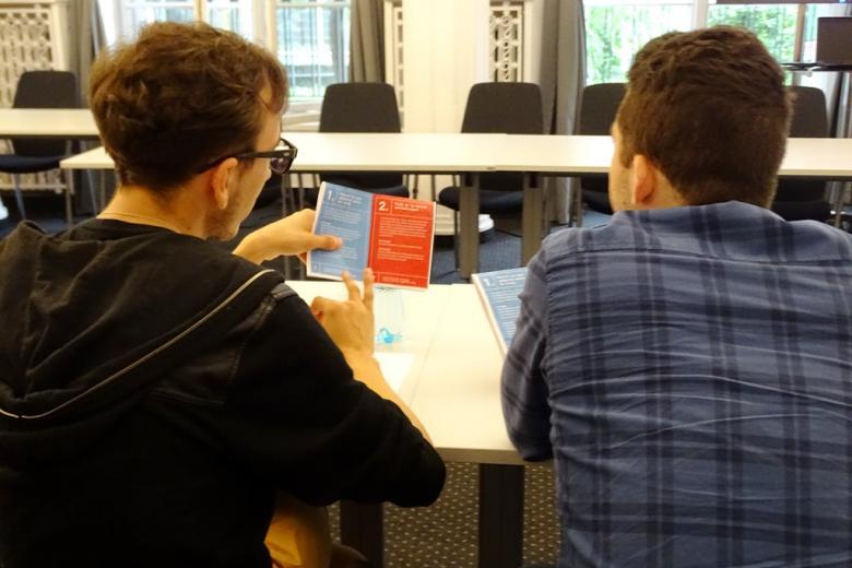 zdjęcie: dwóch mężczyn siedzi tyłem, omawiają ulotkę