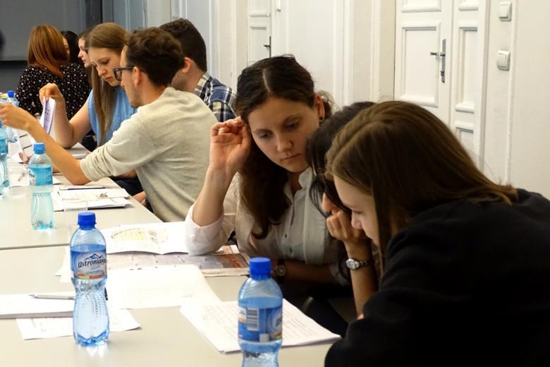 zdjęcie: kilka osób siedzi przy stołach i analizuje dokumenty