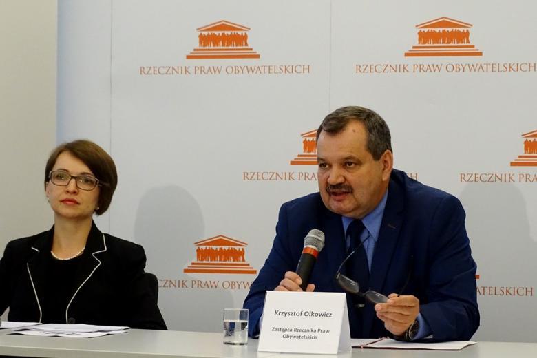 zdjęcie: kobieta w czarnym żakiecie i mężczyzna w granatowym garniturze siedzą przy stole konferencyjnym
