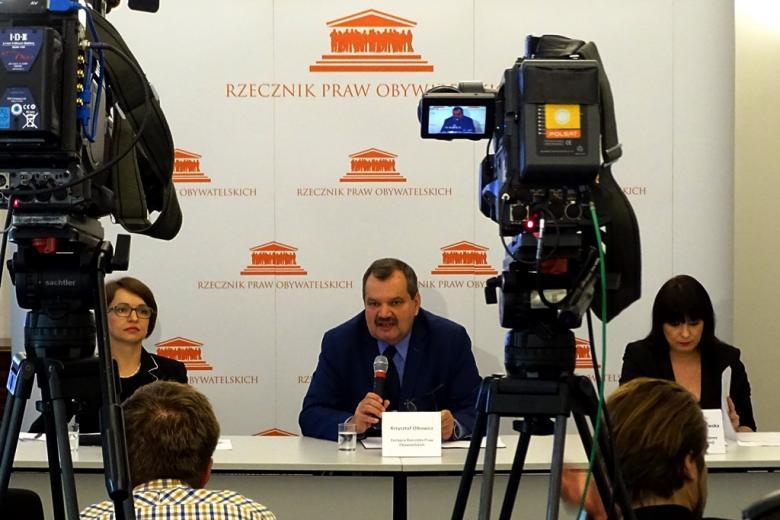 zdjęcie: na pierwszym planie widać dwie ustawione tyłem kamery, przed nimi biały stół konferencyjny za którym siedzą dwie kobiety i mężczyzna