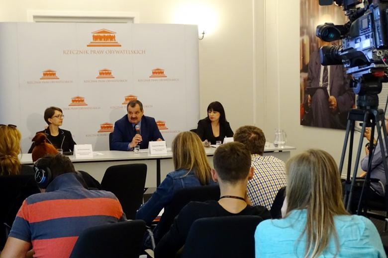 zdjęcie: trzy osoby siedzą za stołem konferencyjnym przed mimo na krzesłach siedzi kilanaście osób