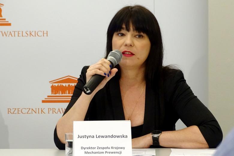 zdjęcie: kobieta w czarnej sukience i czrnym żakiecie siedzi za białym stołem konferencyjnym i mówi do mikrofonu