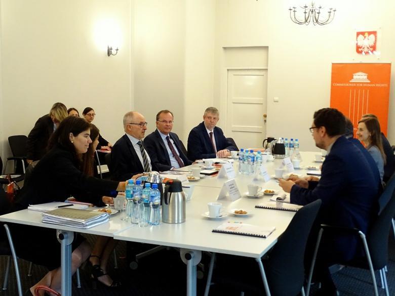 zdjęcie: około 10 osób siedzi po dwóch stronach prostokątnego stołu