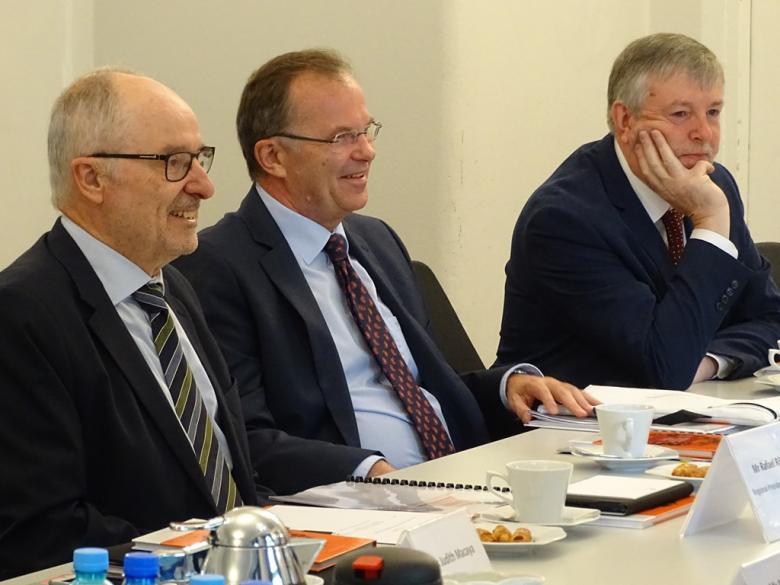 zdjęcie: trzej mężczyźni siedzą przy stole