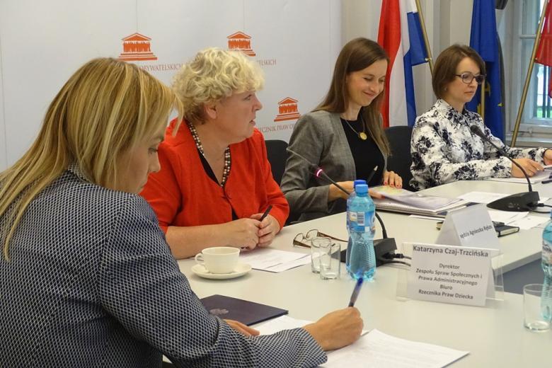 zdjęcie: za białym stołem siedzą cztery kobiety, jedna z nich mówi do mikrofonu