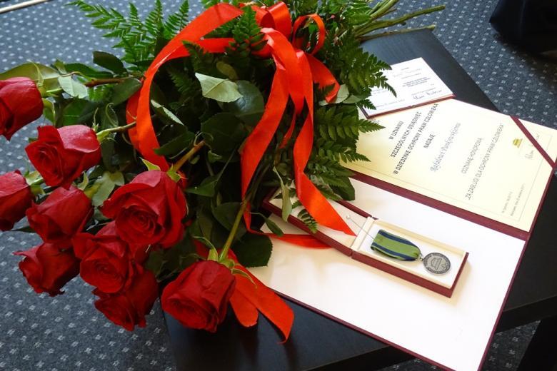 zdjęcie: czerwone róże i odznaka honorowa