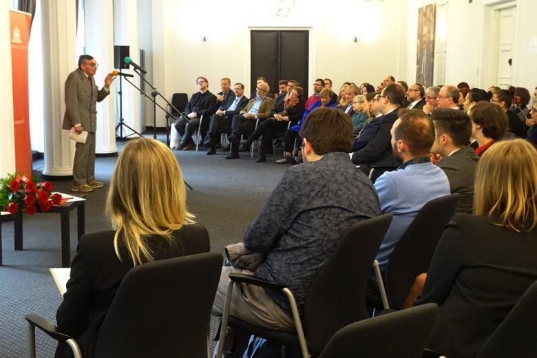 zdjęcie: kilkadziesiąt osób siedzi na sali, przed nimi stoi mężczyzna w garniturze