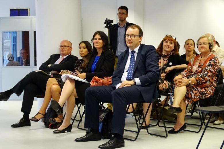 zdjęcie: kilkadziesiat osob siedzi na krzesłach, niektórzy mają słuchawki na uszach