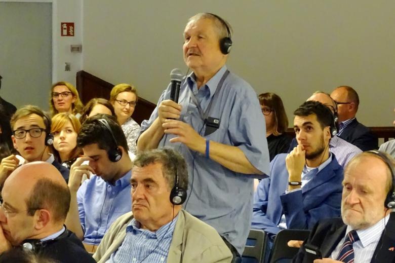 zdjęcie: mężczyzna w jasnej koszuki stoi z mikrofonem posród siedzących na krzesełkach osób