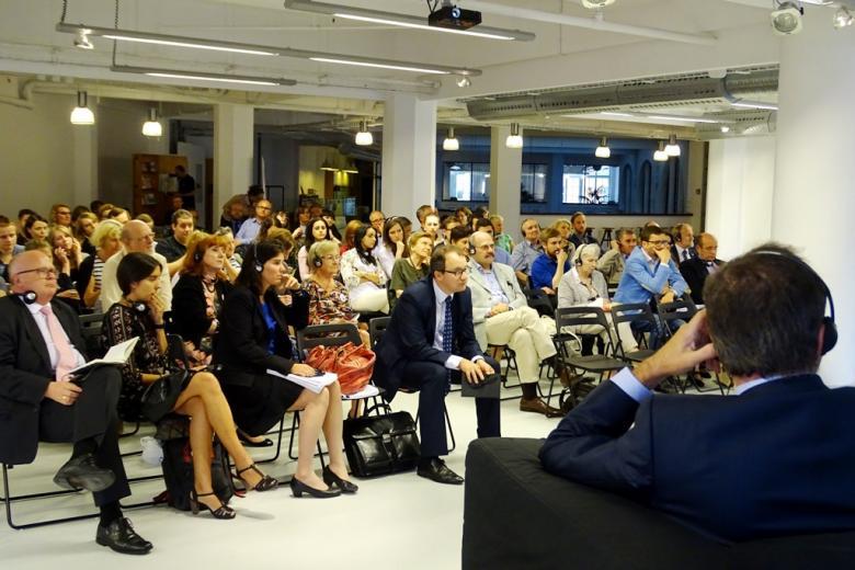 zdjęcie: po prawej stronie widać fragment siedzacego tyłem męzczyzny w garniturze, przed nimi na krzesłach siedzi kilkadziesiąt osób