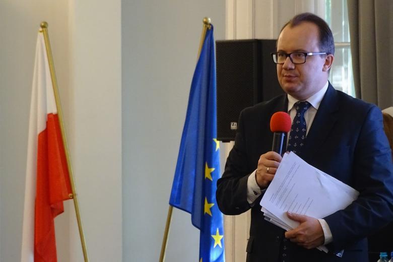 zdjęcie: mężczyzna w garniturze mówi do mikrofonu za nim stoją flagi