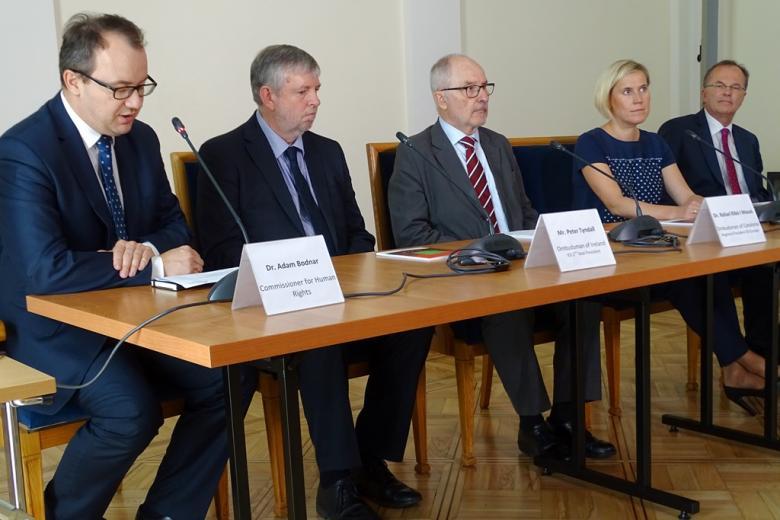 zdjęcie: pięć osób siedzi za stołem konferencyjnym, wśród nich jest jedna kobieta