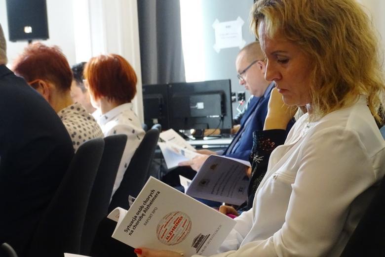 zdjęcie: kobieta siedzi i przegląda publikację