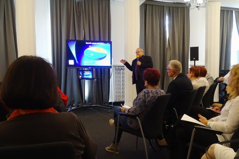zdjęcie: kilka osób siedzi na sali, mężczyzna stoi przed nimi i omawia wykresy prezentowane na ekranie
