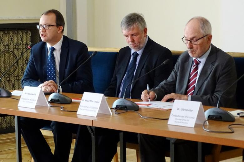 zdjęcie: trzech mężczyzn w garniturach siedzi za stołem konferencyjnym
